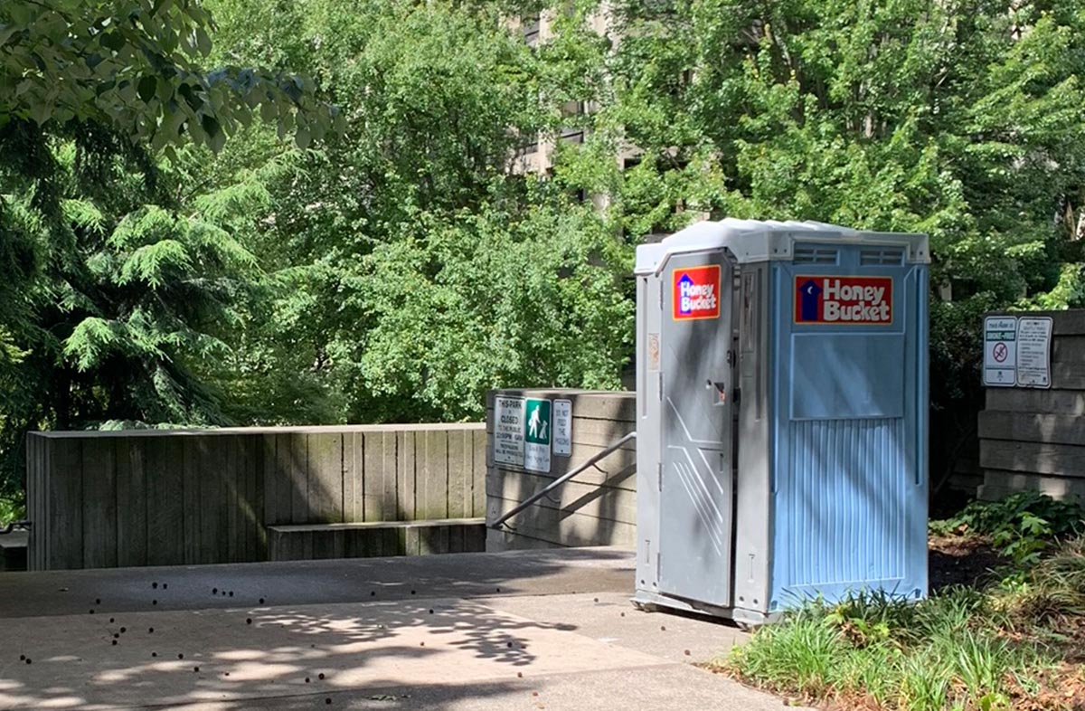Image of a portable toilet at Freeway Park showing how site conditions require restoration and repair.