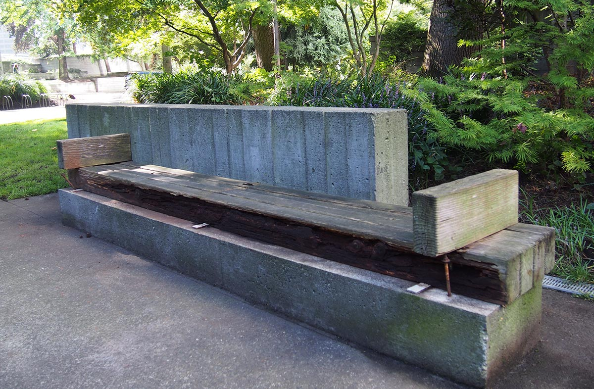 Image of a bench at Freeway Park showing how site conditions require restoration and repair.